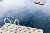 Dock on calm summer lake — Stock Photo