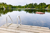Dock on calm lake in cottage country — Stock Photo