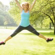 Smiling woman jumping in park — Stock Photo