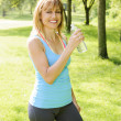 Stock Photo: Active womholding water bottle outside