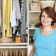 Stock Photo: Smiling womnear closet