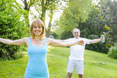 Personal trainer with client exercising outside — Stock Photo