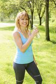 Active woman holding water bottle outside — Stock Photo