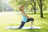 Smiling woman stretching in park — Stock Photo