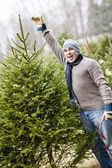 Man with Christmas tree on a farm — Stock Photo