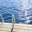 Dock on summer lake with sparkling water — Stock Photo