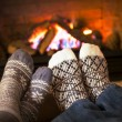 Feet warming by fireplace — Stock Photo #27801669