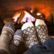 Stock Photo: Feet warming by fireplace