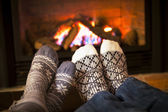 Feet warming by fireplace — Stock Photo