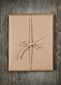Gift in brown paper tied with string — Stock Photo