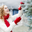 Woman decorating Christmas tree outside — Stock Photo