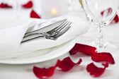 Configuração de um jantar romântico com pétalas de rosa — Foto Stock