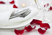Romantic dinner setting with rose petals — Stok fotoğraf