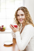 Smiling woman holding red coffee cup — Stock Photo