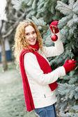 Woman decorating Christmas tree outside — Stock Photo