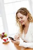 Mujer sonriente utilizando teléfonos inteligentes — Foto de Stock