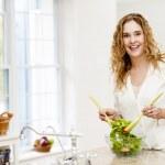 微笑女人扔在厨房沙拉 — 图库照片