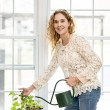 Smiling woman watering plant at home — Stock Photo