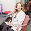 Smiling womon telephone at office desk — Stok Fotoğraf #27848303