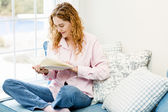 Woman reading book by window — Stock Photo
