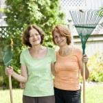 kvinnor med krattor i trädgården — Stockfoto