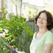 Senior woman pruning rose bush — Stock Photo #27908933