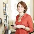 kobieta w domu przy użyciu telefonów komórkowych — Zdjęcie stockowe