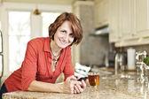 Vrouw met behulp van mobiele telefoon thuis — Stockfoto