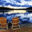 Wooden chairs at sunset on lake shore — Foto Stock