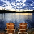 Wooden chairs at sunset on lake shore — Stock Photo #27910367