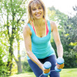 Woman exercising with dumbbells in park — Stock Photo