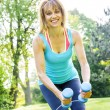 Womexercising with dumbbells in park — Stock Photo #27910699