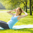 Stock Photo: Womdoing situps in park