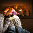 Foto Stock: Feet warming by fireplace