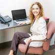 Smiling woman sitting at office desk — Stock Photo