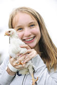 Teenage girl holding chicken — Stock Photo