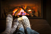 Feet warming by fireplace — Stok fotoğraf