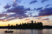 Canoe on lake at sunset — Stock Photo