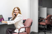 Gülümseyen kadın telefonu ile ofis masası — Stok fotoğraf
