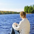 Stock Photo: Womrelaxing at lake shore