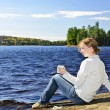 Stock Photo: Young womrelaxing at lake shore