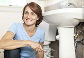 Woman fixing plumbing — Stock Photo
