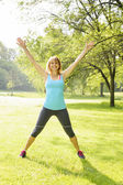 Smiling woman exercising outside — Stock Photo