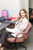 Businesswoman on telephone at office desk — Stok fotoğraf