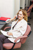 Smiling woman on telephone at office desk — Stok fotoğraf