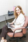 Woman typing on laptop computer at work — Stockfoto