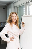 Business woman writing on flip chart — Stock Photo