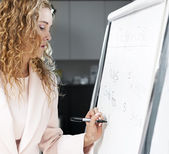 Real estate agent writing on flip chart — Stock Photo