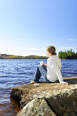 Woman relaxing at lake shore — Stock Photo