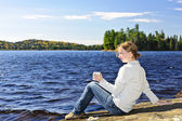 Young woman relaxing at lake shore — Stock Photo